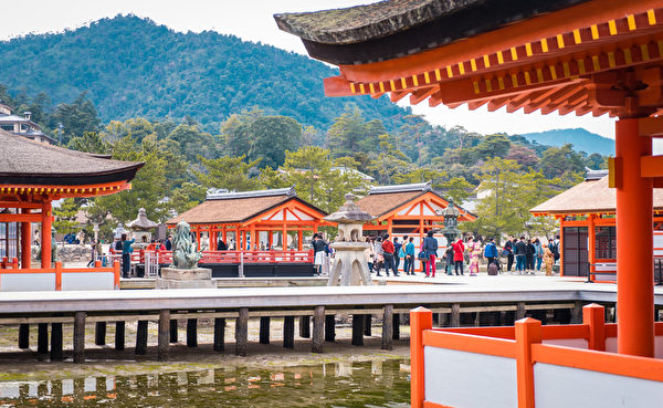 A large group of tourists is taking picture with the Famous floating tori.