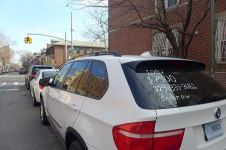 布碌崙50街交九大道沿街停了各款待售的二手車,車後窗上用白色油漆寫著汽車年份等資料。