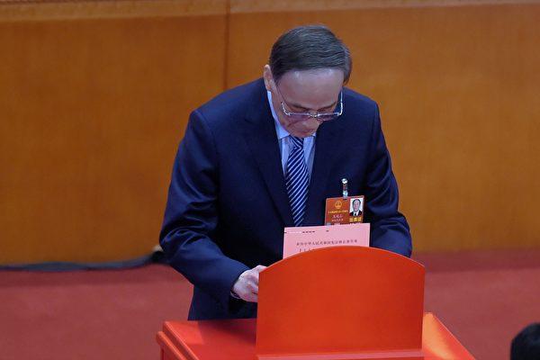 3月11日,王岐山在中共人大对宪法修正草案表决的投票现场。(WANG ZHAO/AFP/Getty Images)
