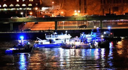 11日一架直升机坠入纽约东河,搜救人员在事发地点打捞搜救。