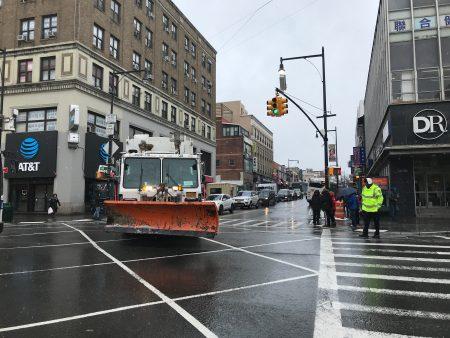 这场风暴令法拉盛缅街人流大减,扫雪车来回清理马路积雪。
