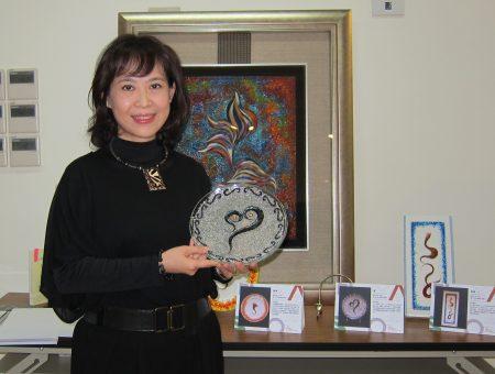 屏东科大副教授谢清秀将化疗掉落的发丝创作成发画,8日于屏科大典范特色展览中心展出;图中手持为罹癌后创作的第一件作品〈爱〉。