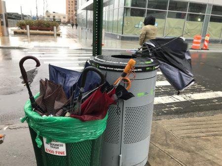 風太大,行人雨傘被吹斷,法拉盛中心區的垃圾桶都是被風吹爛後被路人丟棄的雨傘。