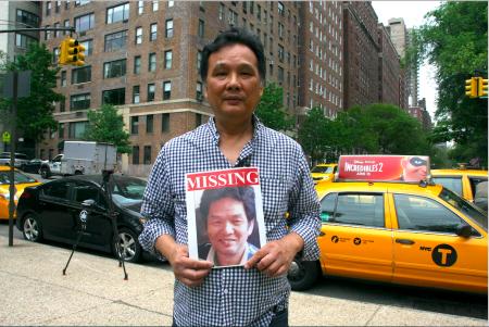 失踪的缅甸出租车司机曹耀明(Yumain Kenny Chow)的大哥曹耀均,举着弟弟的照片。
