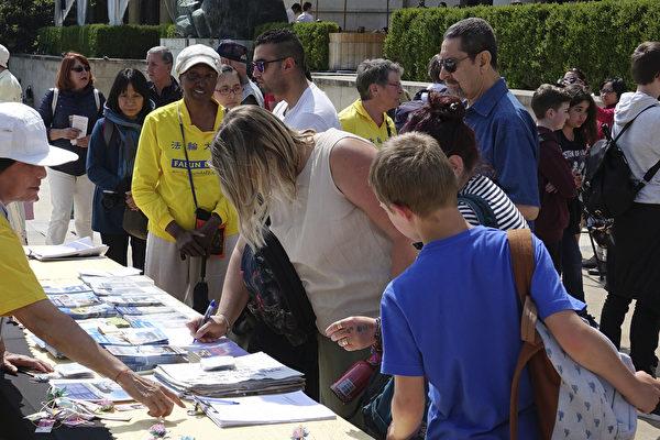 法國慶祝第十九屆世界法輪大法日的活動上,過往民眾紛紛在簽名簿上留言簽名,聲援儘快結束這場史無前例的迫害,譴責中共的罪行。(葉蕭斌/大紀元)