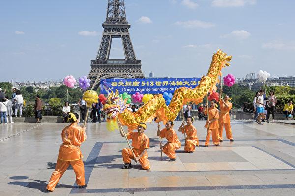 2018年5月20日在法國巴黎鐵塔對面的人權廣場上,法國部分法輪功學員用歌舞演出和功法演示慶祝第十九屆世界法輪大法日。(葉蕭斌/大紀元)