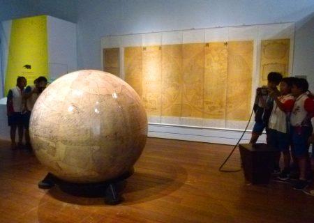 故宫国宝台东展出,学生用AR观察《南怀仁的坤舆全图》,了解古人对地球的认识。