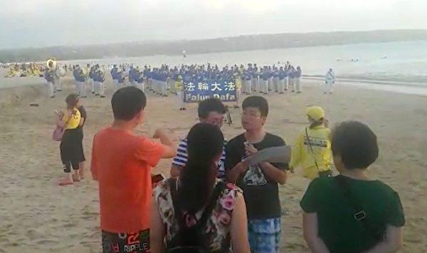 峇里岛法轮功学员在金巴兰海滩庆祝世界法轮大法日。中国游客拿过大纪元报纸,议论著。(视频截图)