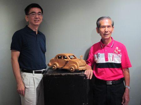 廖義雄(右)雕刻的賓士轎車。左為雲科大客家文化研究中心主任黃衍明教授。