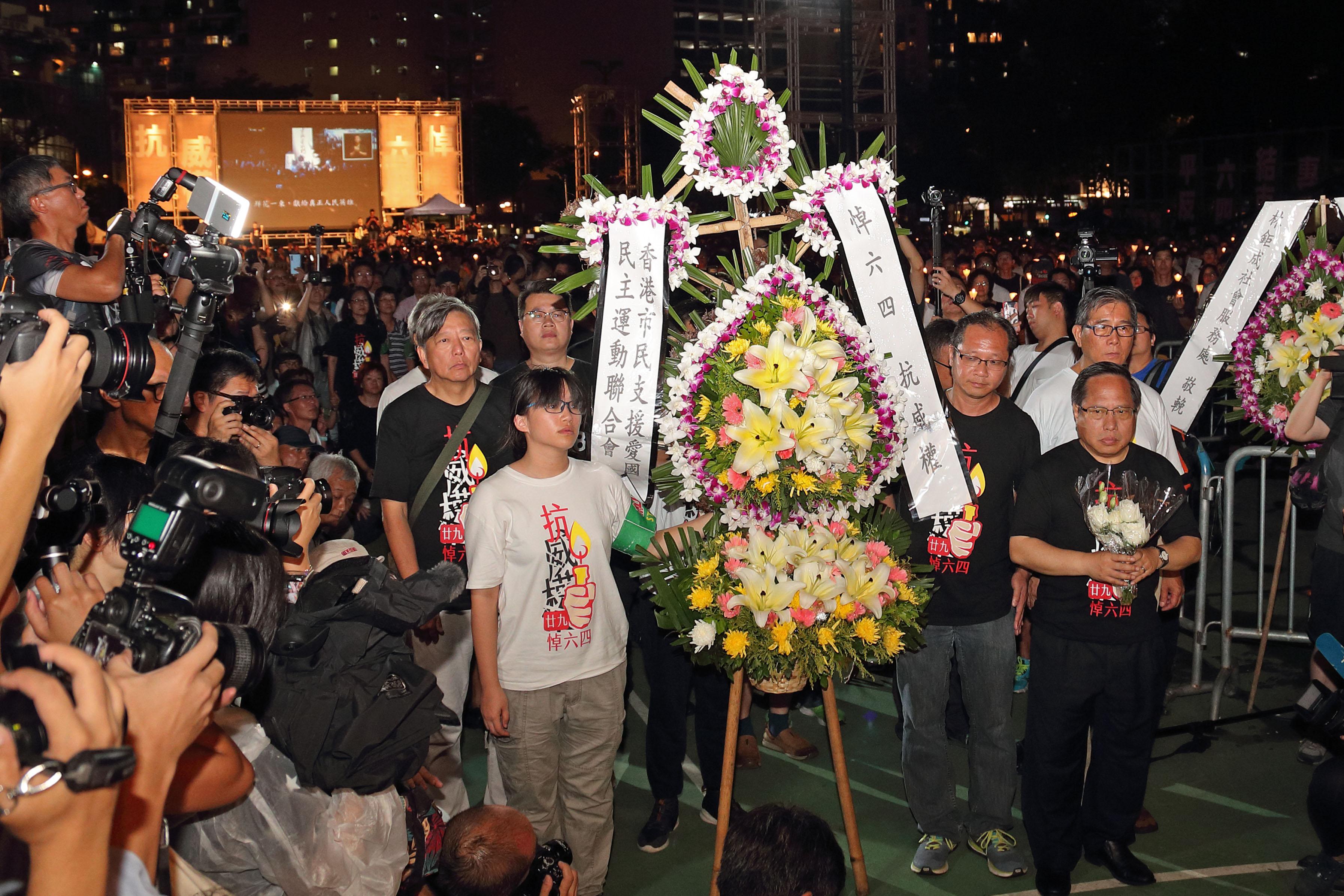 2018年6月4日,香港,支聯會常委與數名年輕人手持花牌向「民主烈士永垂不朽」紀念碑獻花。(李逸/大紀元)