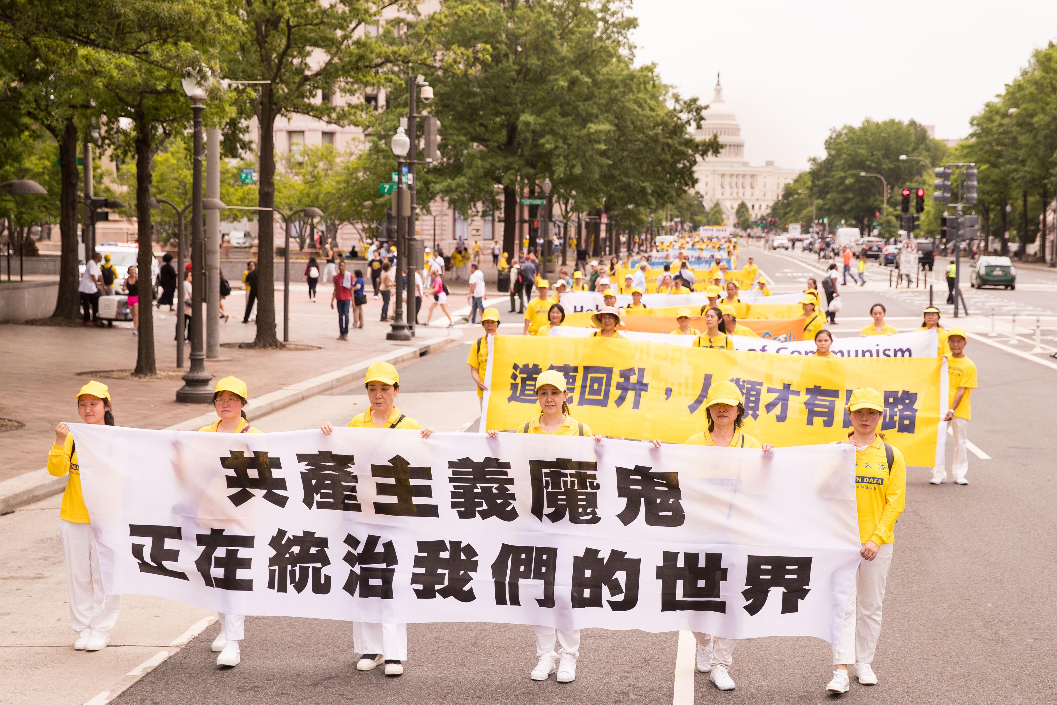 2018年6月20日,部份法輪功學員美國首都華盛頓舉行反迫害大遊行。橫幅展示「共產主義魔鬼正在統治我們的世界」。(戴兵/大紀元)