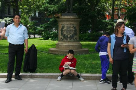 市议会集会时,华裔学生招喜然(Ethan Chieu)在一旁安静地读书。