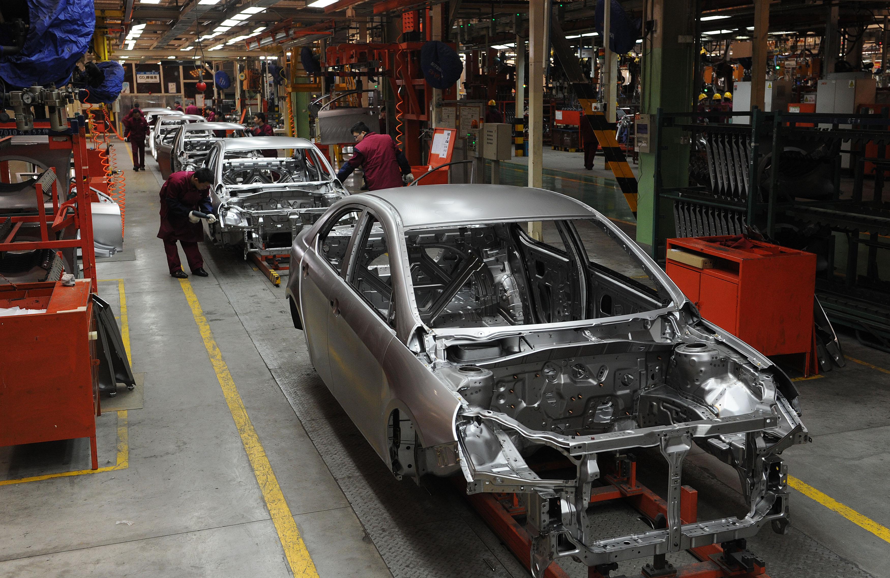 大陸車市持續下滑,多地鬆綁限購,押注「金九銀十」。圖為中國汽車工廠。(STR/AFP)
