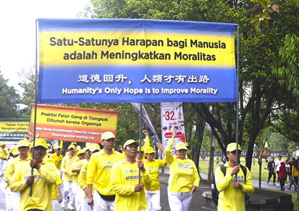 纪念7.20法轮功学员反迫害19周年,峇里岛部分法轮功学员参与游行。图为横幅队。(萧律生/大纪元)
