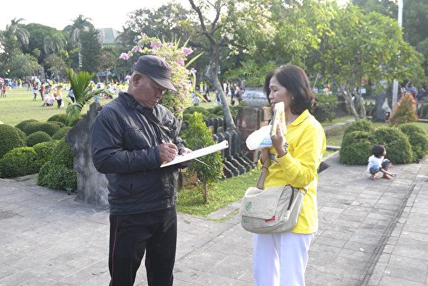 峇里岛法轮功学员向民众讲述真相,并请他们签字声援法轮功。(萧律生/大纪元)