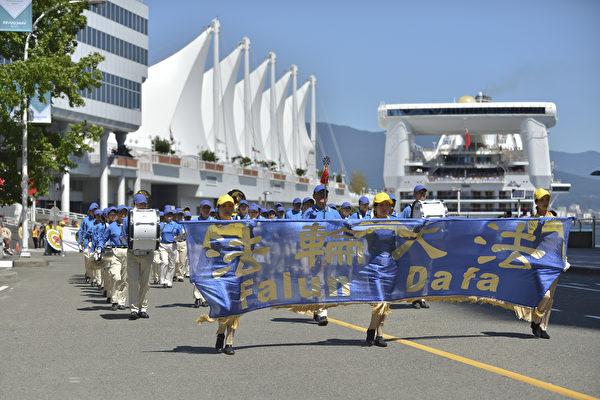 法轮功学员游行队伍途经温哥华市中心著名旅游景点,温哥华的地标五帆酒店。(大宇/大纪元)