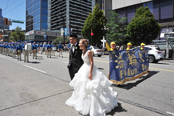 正在举行婚礼的新郎和新娘,在亲朋好友们的欢呼声中与法轮功游行队伍的天国乐团合影留念。 (雨生/大纪元)