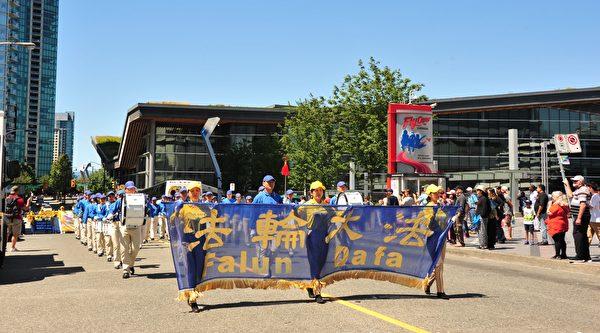 法轮功学员在市中心举行大游行,途径温哥华的市中心。(雨生/大纪元)