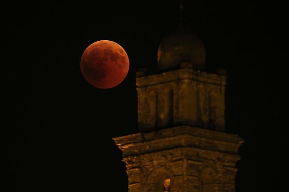 圖為2018年7月27日月食期間,在法國地中海科西嘉島上的Venzolasca教堂旁邊看到的血月PASCAL POCHARD-CASABIANCA/AFP/Getty Images)。
