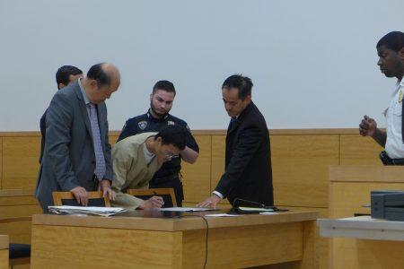 盧勇在法庭給妻子的保護令上簽字。