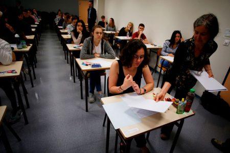 图为监考老师发放作答卷。