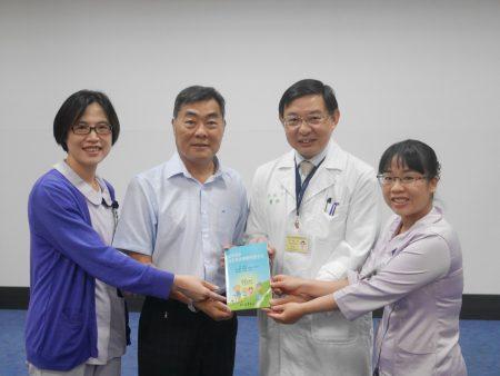 院长洪冠予(右二)赠书给洗肾病友贺先生(左二)