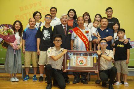 由崙背乡公所推荐的好人好事代表李崇宏(披彩带者)在家人的陪伴下,接受县长李进勇(二排中)的表扬。