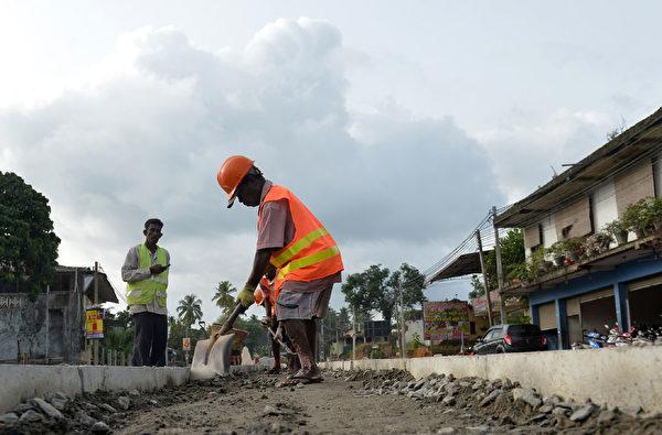 斯里蘭卡因中共的一帶一路計劃揹負鉅額債務,被迫簽署一份長達99年的租約,將具有戰略意義的漢班托塔港(Hambantota port)移交給中共。圖為斯里蘭卡工人在修路。(LAKRUWAN WANNIARACHCHI/AFP/Getty Images)