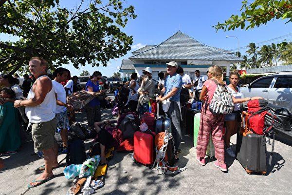 国外游客等待安排,离开龙目岛。 (Photo credit should read ADEK BERRY/AFP/Getty Images)