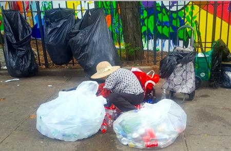 一位華人阿婆正在挑揀自己回收的瓶子。