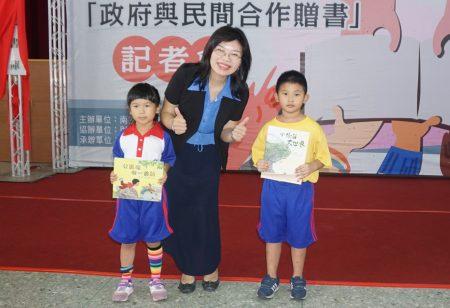 南投县政府教育处长李孟珍(中)转赠教育部送给每位新生的一本书。