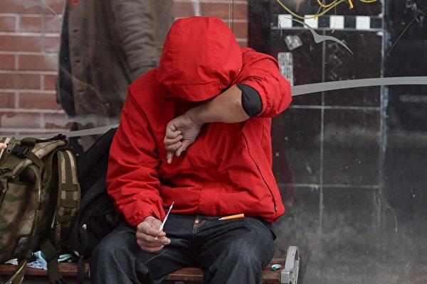 图: 温哥华市中心东部已成为瘾君子们公开吸毒的场所,图为一名刚刚为自己注射完的吸毒者。(加通社)