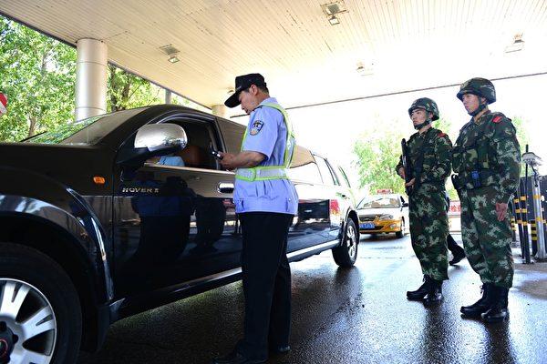 图为通往北京的某高速公路检查点,持枪武警协助安检人员检查过往车辆。一到敏感时刻北京当局大为紧张。(STR/AFP)