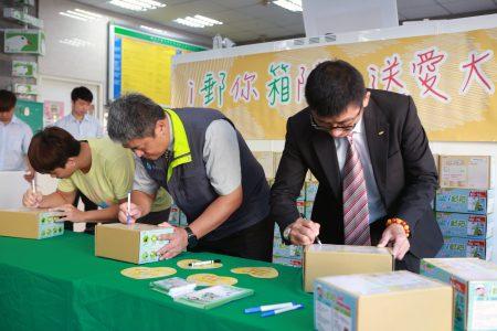 左起蔡伯斌同学、杨秀川处长及钟耀明经理书写邮寄地点。