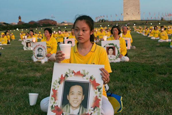 法輪功學員手捧燭光,手持被迫害致死法輪功學員照片。(明慧網)