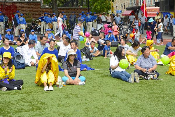 华埠民众做草坪上观看表演。(马青/大纪元)