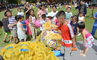 小朋友兴奋地摸著金色舞狮的头,与之玩成一片。(马青/大纪元)