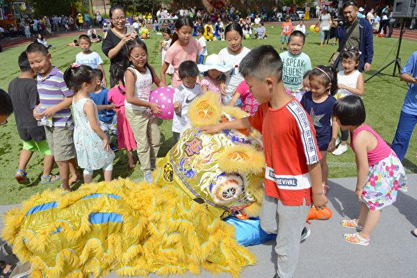 小朋友兴奋地摸着金色舞狮的头,与之玩成一片。(马青/大纪元)