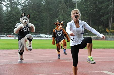 健身教練在體育場,為參加本地泰瑞福克斯長跑的市民做熱身操。(童宇/大紀元)