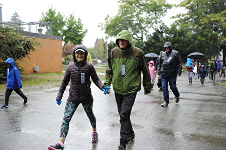 在當天的本拿比市的泰瑞福克斯長跑中,有一對老年夫婦,手牽手地在雨中長跑。(童宇/大紀元)