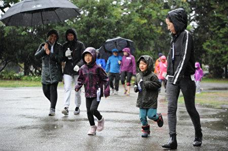 在當天的本拿比市的泰瑞福克斯長跑中,有家長帶著小孩,堅持在雨中長跑。(童宇/大紀元)