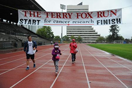 跑完2公里的希望馬拉松路程,Lucy(中)回到了體育場。(童宇/大紀元)