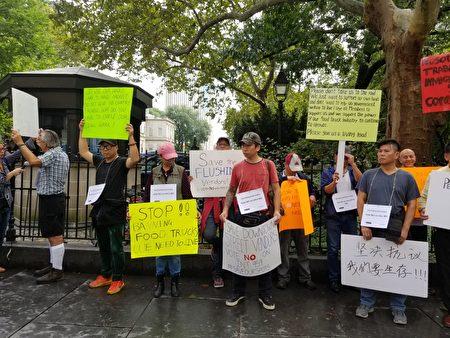 多位法拉盛餐車與攤販商趕至市議會圍牆外舉牌抗議,並試圖向路過議員遊說投反對票。