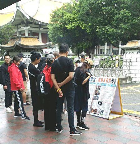 台北國父紀念館前,大陸遊客認真閱讀法輪功真相展板。(明慧網)