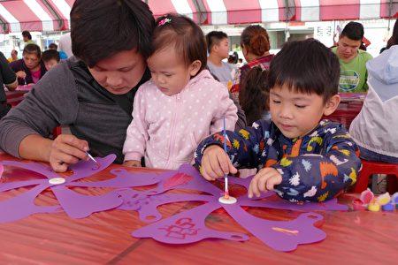 家長一手抱著小女兒,另一隻手則和較大的兒子一起彩繪,親子關係非常融洽、溫馨。