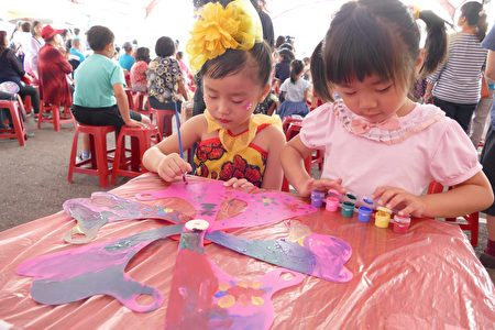 一對小姊妹專注地彩繪風車。
