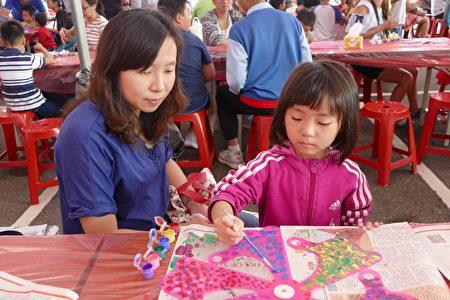 在媽媽的陪伴下,幼兒園的學童很起勁地參與彩繪風車。