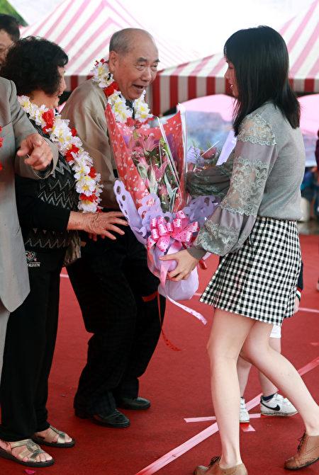 站在台上的钻石婚夫妻很高兴接受晚辈赠送鲜花祝福。