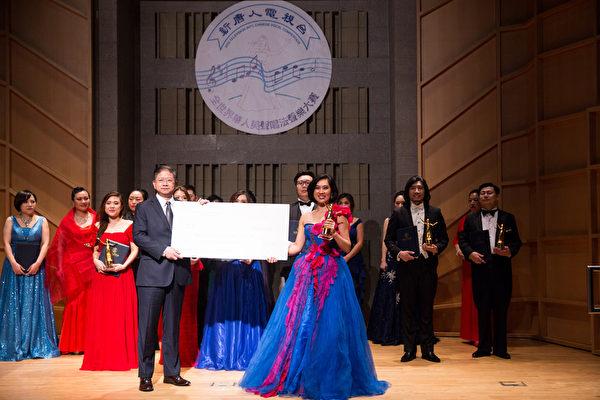 11月10日,新唐人電視台總裁唐忠(前排左一)向第七屆「全世界華人美聲唱法聲樂大賽」比賽中獲得金獎的女聲組選手盟盟(前排右一)頒獎。金獎獎金為1萬美元。(戴兵/大紀元)