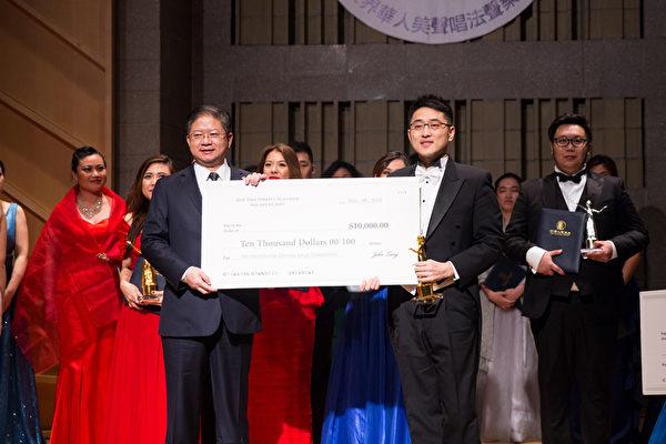 11月10日,新唐人電視台總裁唐忠(前排左一)向第七屆「全世界華人美聲唱法聲樂大賽」比賽中獲得金獎的男聲組選手古韻(前排右一)頒獎。金獎獎金為1萬美元。(戴兵/大紀元)